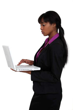 quotas: attractive black woman using laptop isolated on white