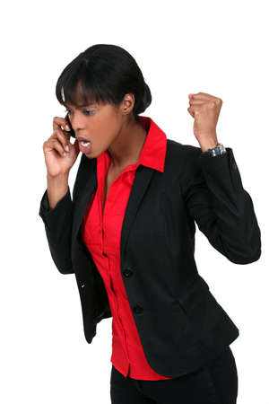 rant: An angry businesswoman over the phone. Stock Photo