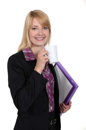 congenial: attractive female student holding mug of coffee and files
