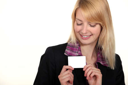 eyes downcast: blonde businesswoman with downcast eyes showing business card Stock Photo