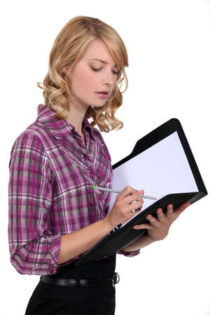 checkered skirt: Attractive woman writing in a folder Stock Photo