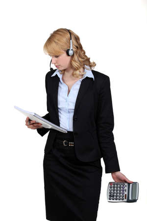 call center female: portrait of blonde in suit with headset holding notepad and calculator
