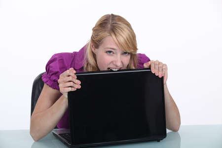 anguished: Woman eating her laptop in frustration