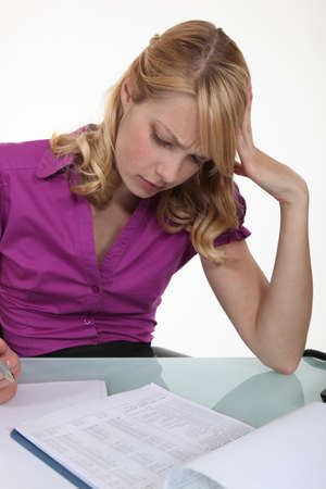 perplexing: Woman filling in paperwork Stock Photo