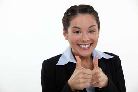 Happy businesswoman giving thumbs-up gesture photo