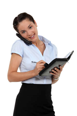Businesswoman scheduling an appointment into her agenda photo