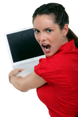 crazed: Angry brunette about to smash laptop Stock Photo
