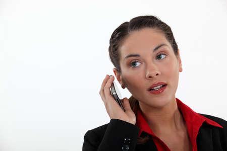 dolor de oido: Mujer con el tel�fono celular aguzando los o�dos