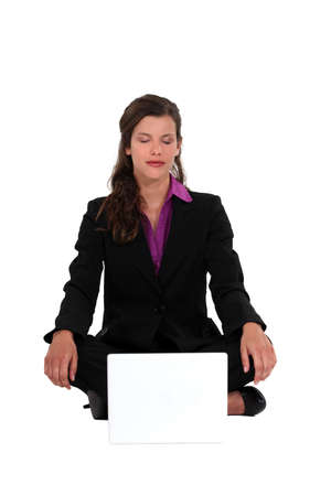 deeply: A businesswoman in a lotus position.