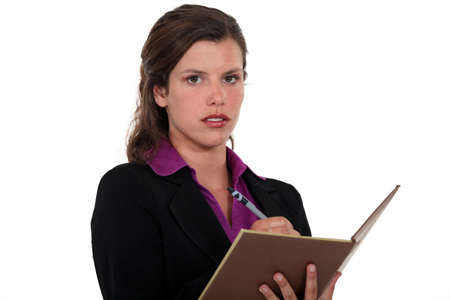 unemotional: Businesswoman writing in her agenda