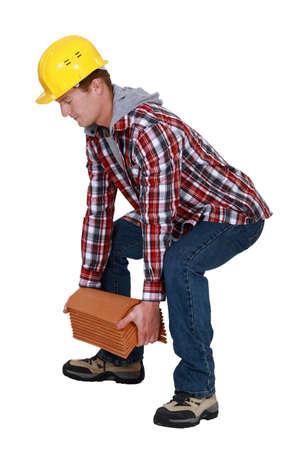 squat: Tradesman lifting shingles