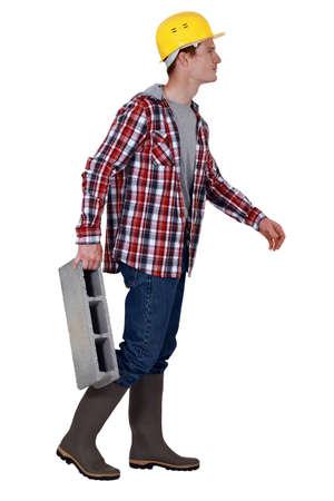 Mason carrying breeze block photo