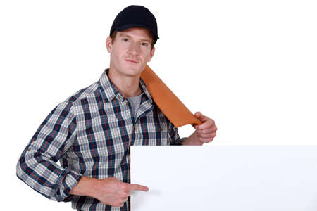 Roofer pointing to a blank sign Stock Photo - 19845337