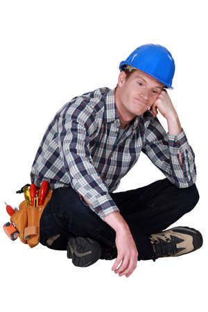 only young men: Bored manual worker sat cross-legged