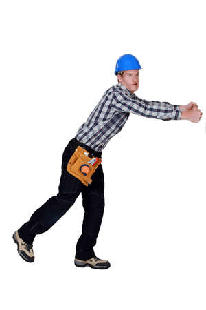 irked: Construction worker pulling something Stock Photo
