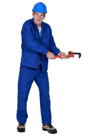 pull along: Tradesman trying to pull an invisible object using a pipe wrench