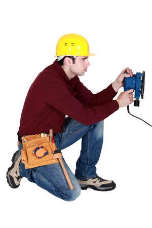 work experience: Man kneeling with power sander