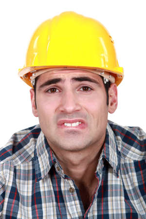 pained: Builder with pained expression on face