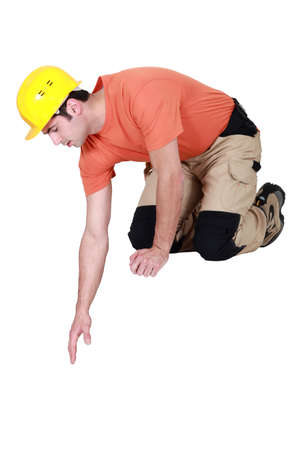 kneel down: Construction worker reaching down to empty copyspace
