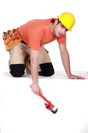 knees bent: Tradesman dangling a pipe wrench from a ledge Stock Photo