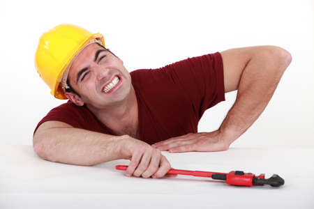 squeeze: Workman with a wrench in a tight spot Stock Photo