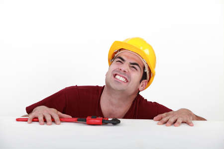 straining: Grunting tradesman trying to lift himself up onto a ledge