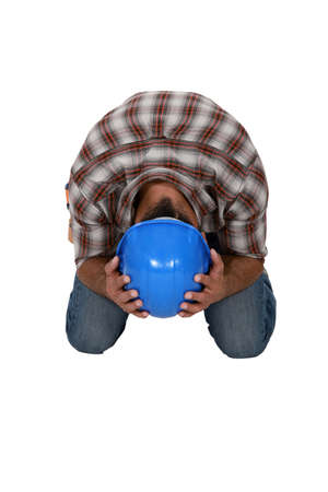 kneeling laborer hiding his head photo