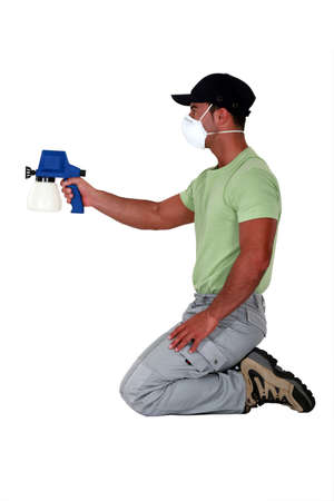 kneeled: A painter using a spray gun. Stock Photo