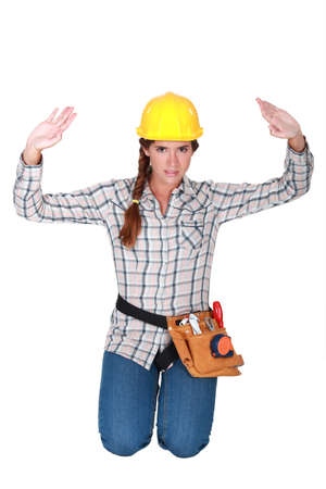 apprehend: Tradeswoman holding up her hands
