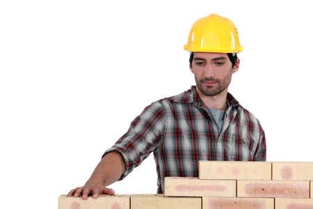 erecting: mason erecting a brick wall