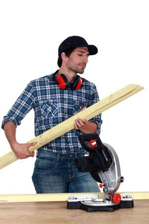 Carpenter cutting wooden slats photo