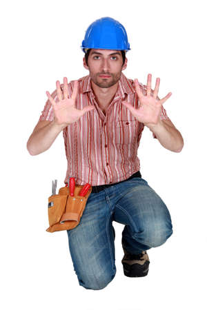 unyielding: Tradesman holding up his hands