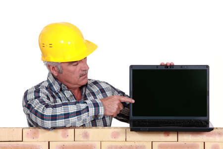 senior craftsman pointing at his laptop photo