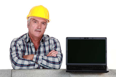 Artisan resting on concrete wall with computer photo