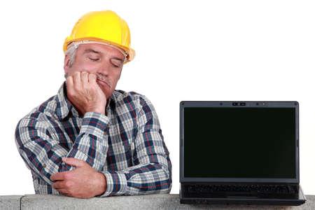 incertitude: senior craftsman posing next to a laptop