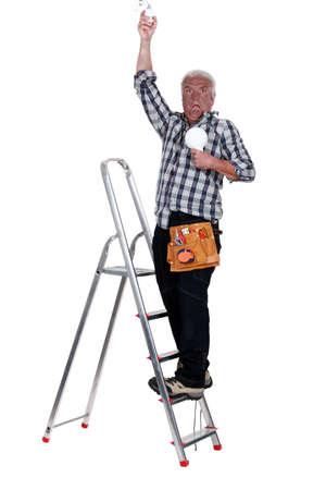convulsion: electricista en una escalera que tiene una descarga eléctrica Foto de archivo