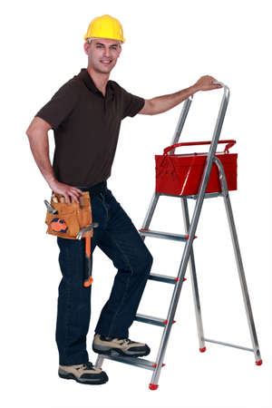 Worker with a toolbox and stepladder Stock Photo