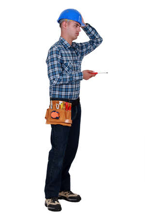 tedious: Annoyed tradesman performing a tedious task Stock Photo