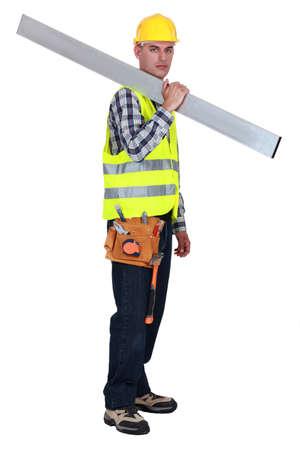 grouch: Tradesman carrying a girder Stock Photo
