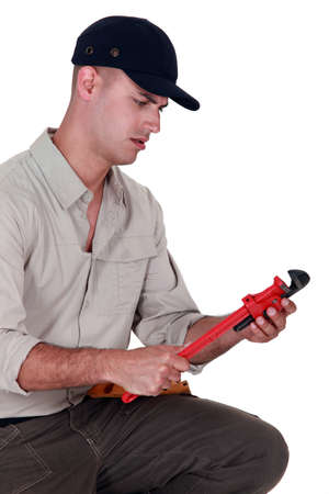 befuddled: Confused man looking at a pipe wrench