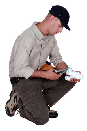 fasten: Plumber using pliers to fasten two parts together Stock Photo