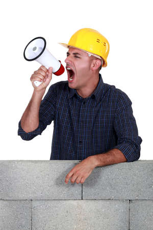 crazed: craftsman shouting through a megaphone Stock Photo