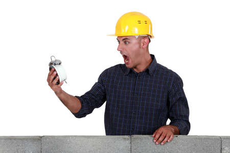 alarmed: Labourer alarmed by the time Stock Photo