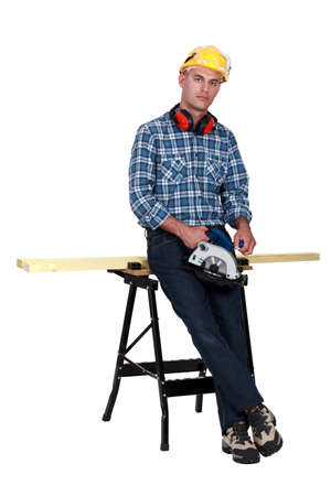 Tradesman standing in front of a workbench and holding a circular saw photo