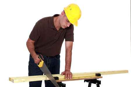 hardworker: Tradesman sawing a piece of wood