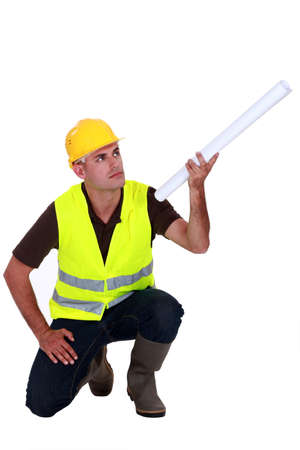 tradesperson: Tradesman holding up a rolled-up blueprint Stock Photo
