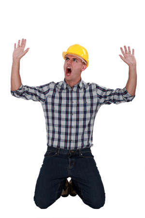 Laborer sitting on his knees screaming Stock Photo - 19810338