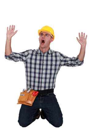 front raise: craftsman on his knees raising hands and shouting Stock Photo