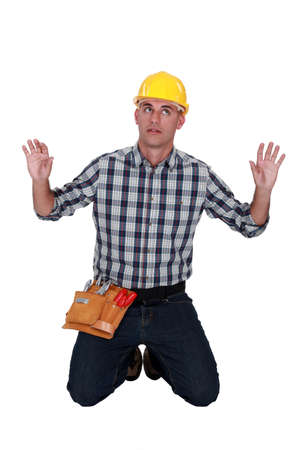 kneeled: A male construction  worker trapped in an invisible box. Stock Photo