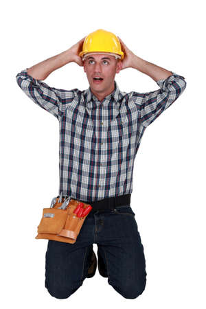 implausible: Astonished tradesman with his hands behind his head Stock Photo